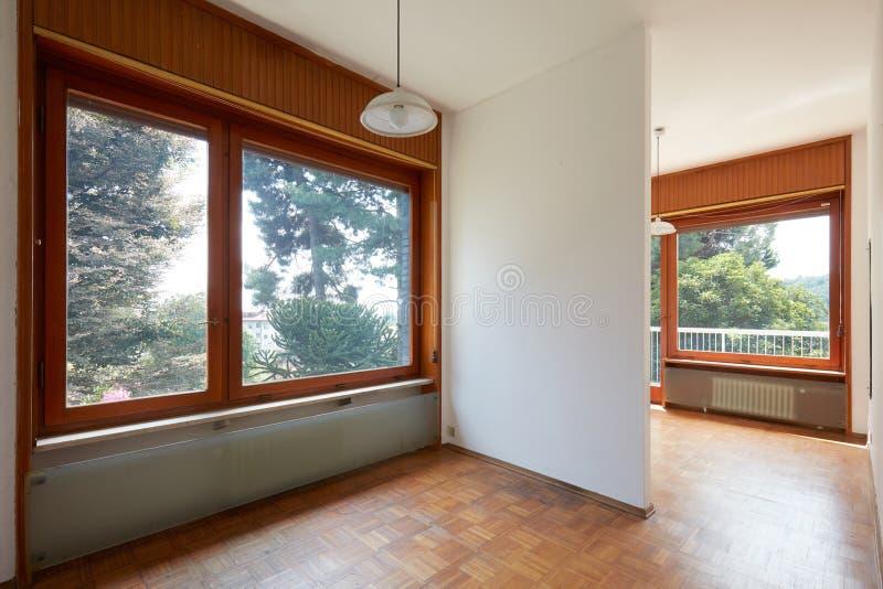 Interno vuoto della camera doppia con il pavimento di legno in casa di campagna immagine stock