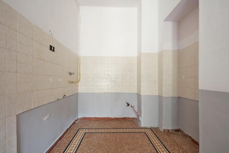 Interno vuoto della cucina con il pavimento piastrellato prima di ripristino immagini stock
