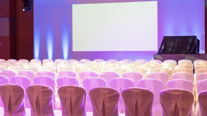 Interno vuoto della sala per conferenze o della stanza di seminario di lusso con lo schermo del proiettore e le sedie bianche fotografia stock