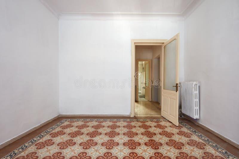 Interno vuoto della stanza con il pavimento piastrellato antico e la porta di legno immagini stock