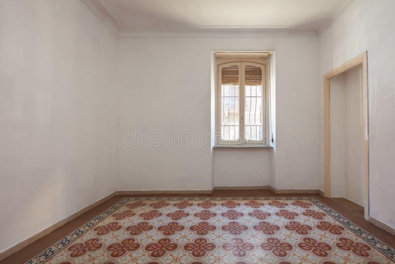 Interno vuoto della stanza con il pavimento piastrellato e decorato in un giorno soleggiato fotografie stock libere da diritti