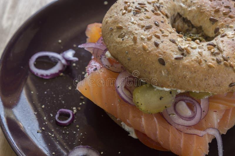 Intero bagel del grano con il formaggio cremoso, del salmone, le cipolle ed il sottaceto cascer immagini stock