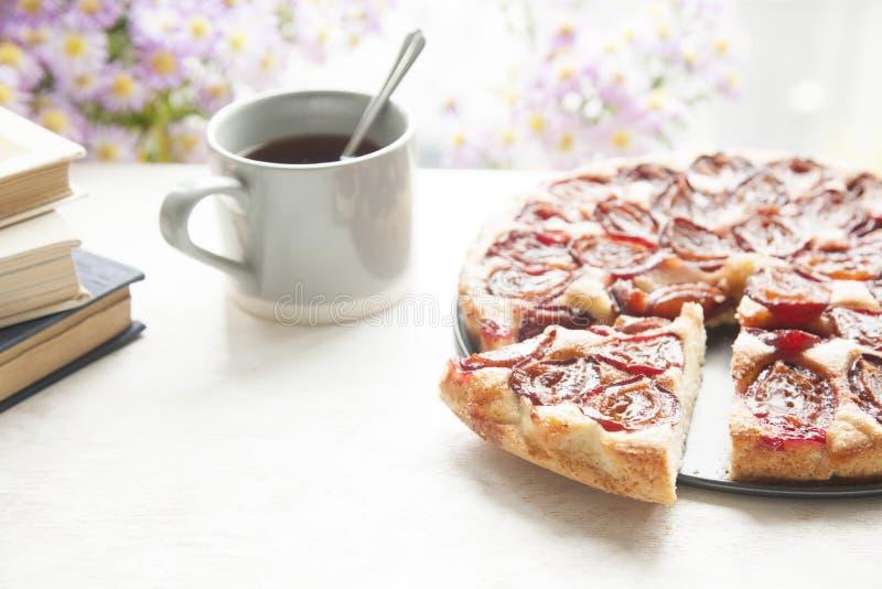 Intero dolce della prugna con la tazza, i libri ed i fiori del tè su backgr di legno fotografia stock libera da diritti