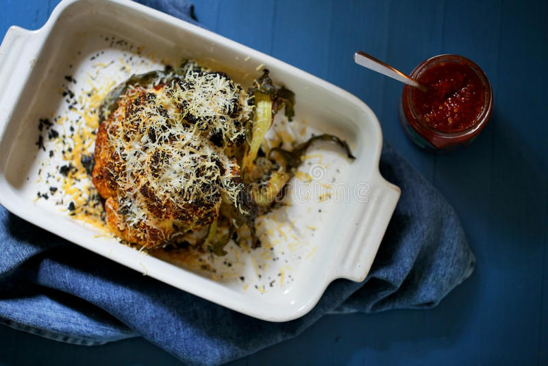 Intero gratin al forno del parmigiano del couliflower con la salsa di peperoncino rosso di sirarcha fotografia stock