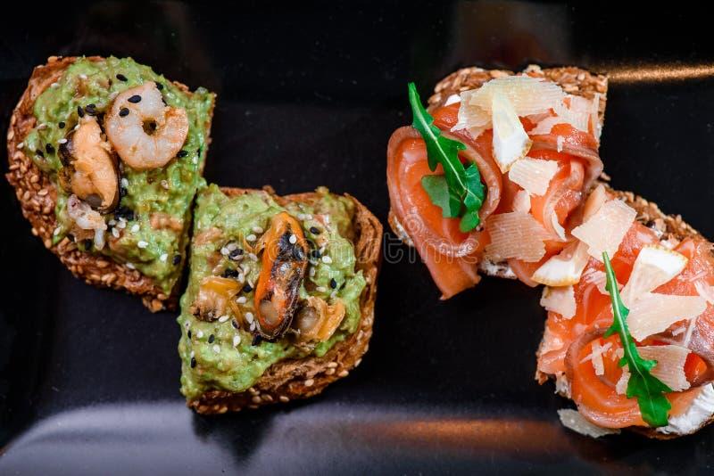 Intero pane del grano con la pasta dell'avocado, cozze e gamberetti ed intero pane del grano con il salmone ed il formaggio su un fotografie stock libere da diritti