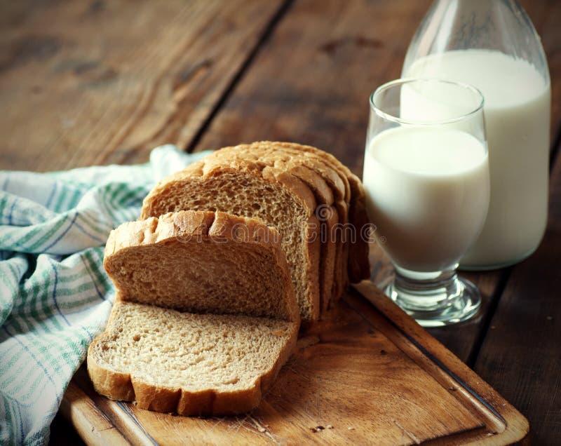 Intero pane del grano con un bicchiere di latte fotografia stock