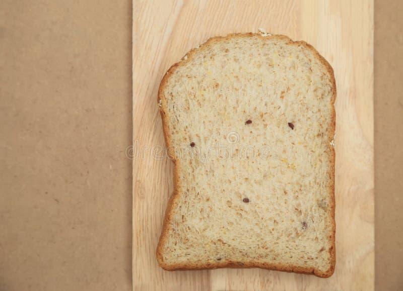 Intero pane del grano sul piatto di legno e sul fondo marrone di struttura fotografia stock
