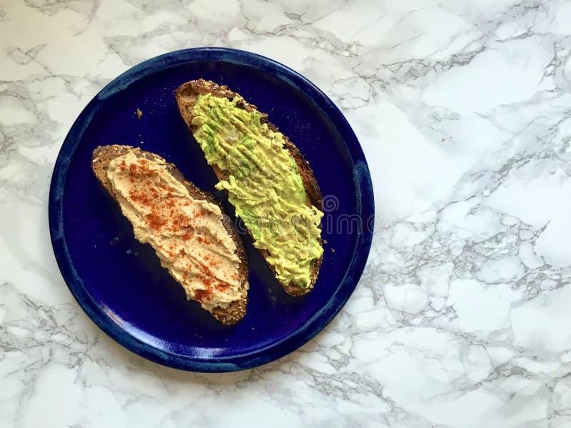 Intero pane tostato artigianale del grano con l'avocado ed il hummus fracassati fotografie stock
