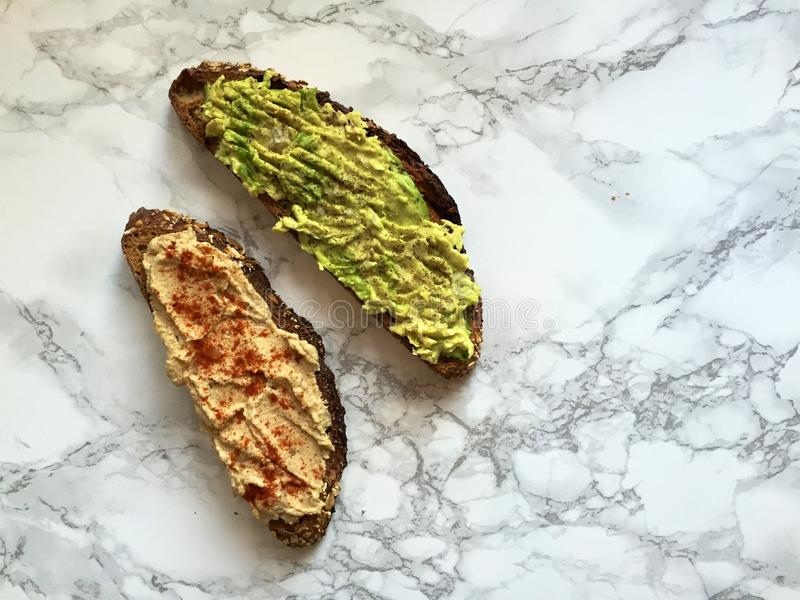Intero pane tostato artigianale del grano con l'avocado ed il hummus fracassati immagine stock libera da diritti