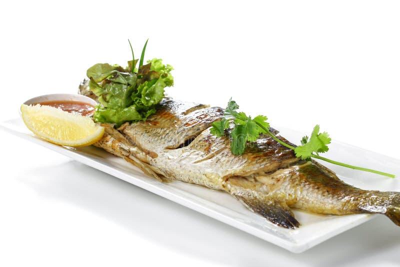 Intero pesce arrostito di Barramundi con Chili Garlic Seafood Sauce rosso e un pezzo di limone sul piatto bianco della porcellana immagini stock