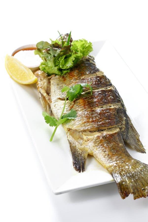 Intero pesce arrostito Pra-Kra-Pong della spigola con Chili Garlic Seafood Sauce rosso e un pezzo di limone sul piatto bianco del immagine stock libera da diritti