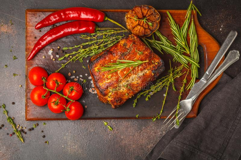 Intero pezzo di arrosto di maiale con timo, rosmarino, aglio su un legno fotografia stock