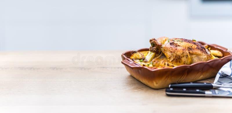 Intero pollo arrostito con le patate in piatto bollente Alimento saporito a casa sul contatore di cucina fotografia stock