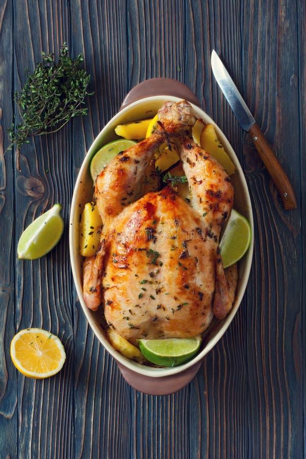 Intero pollo fritto con le patate ed i limoni fotografia stock libera da diritti