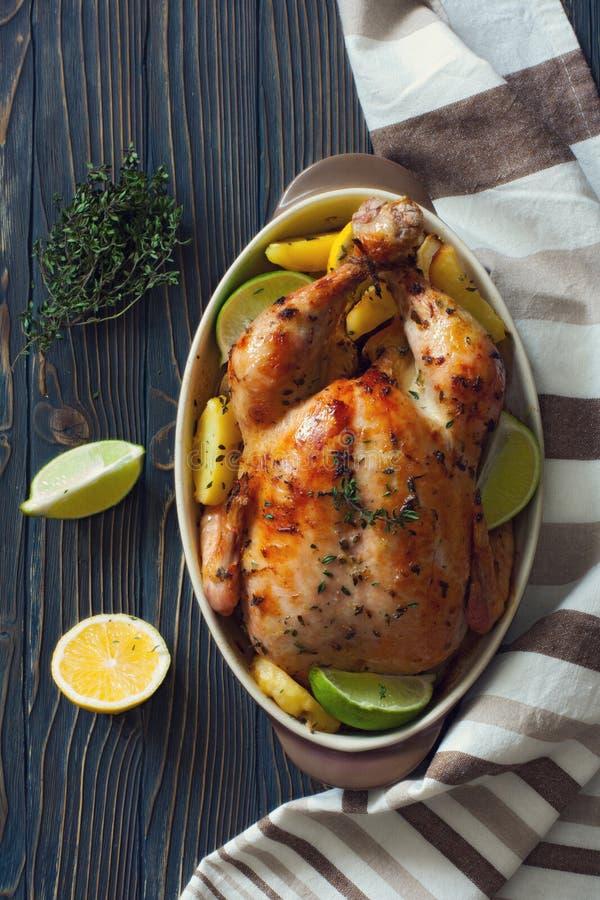Intero pollo fritto con le patate ed i limoni immagine stock libera da diritti