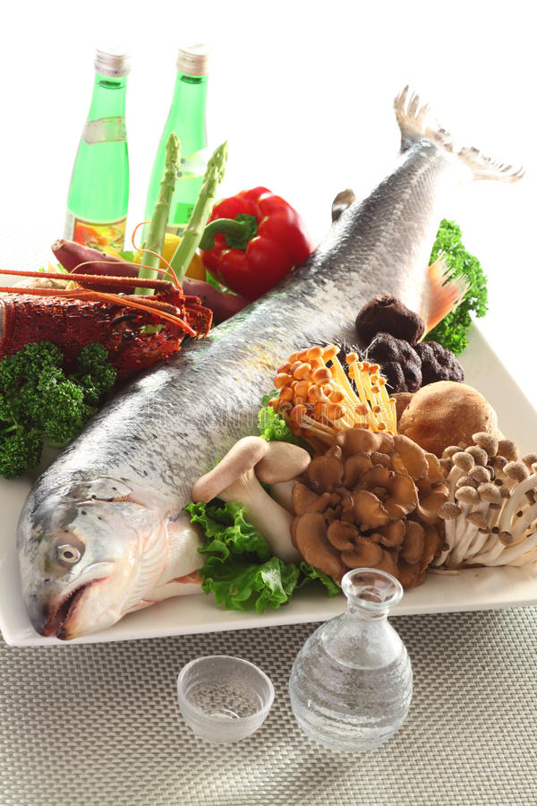 Intero salmone fresco con il fungo, i broccoli, il peperoncino rosso e l'olio in corredo immagini stock