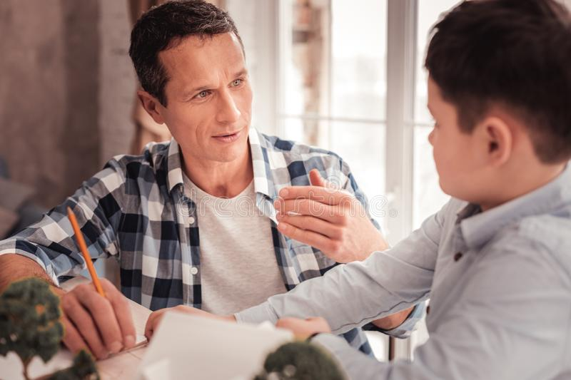 Foster father improving his interpersonal relations with his son. Interpersonal relations. Caring foster father improving his interpersonal relations with his stock images