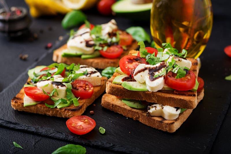 Interponga i pani tostati con i pomodori, la mozzarella, l'avocado ed il basilico fotografie stock libere da diritti