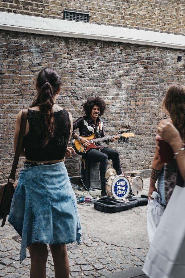 Interprète de rue chantant sur la ruelle de brique, Londres, R-U photographie stock libre de droits