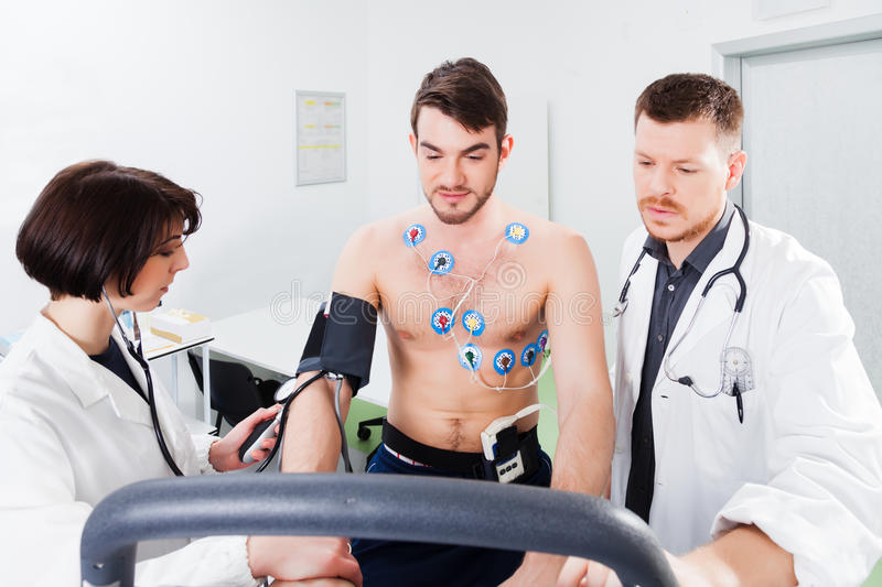 Interpretation of the electrocardiogram of young athlete. Athlete does a cardiac stress test in a medical study, monitored by the doctor and nurse royalty free stock images