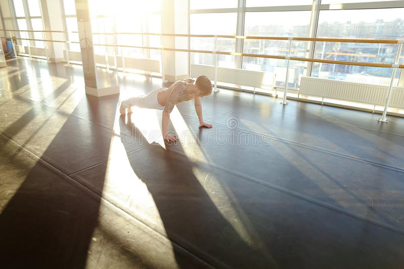 Interpreter in sportswear doing press exercises in sport hall. Interpreter doing press exercises in hall, young man fond of sports since childhood. Fair-haired royalty free stock images