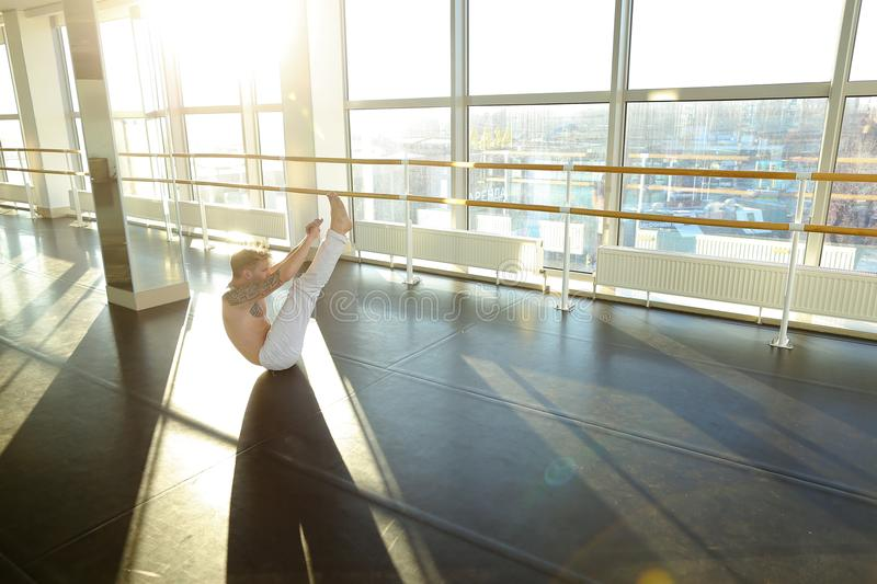 Interpreter in sportswear doing press exercises in sport hall. Interpreter doing press exercises in hall, young man fond of sports since childhood. Fair-haired royalty free stock image