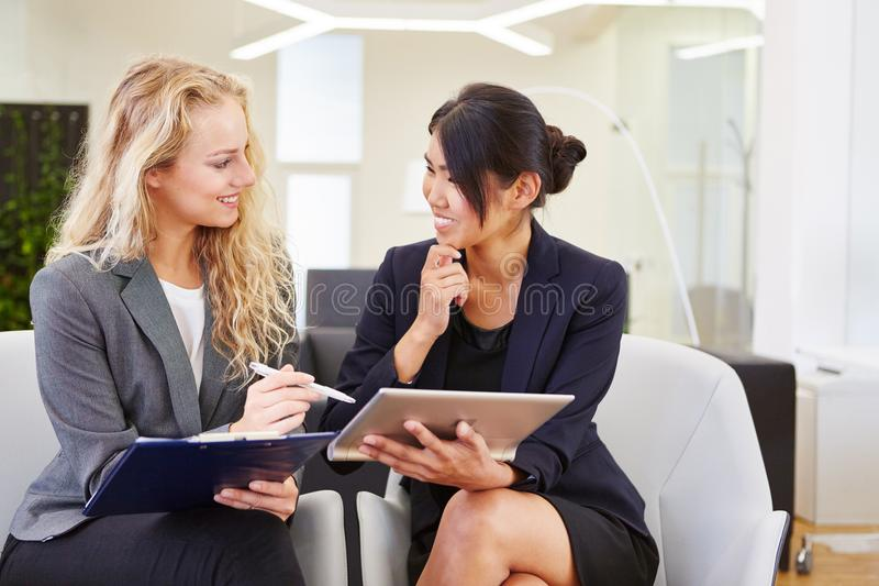 Interracial business women team. In dialogue at office stock photo