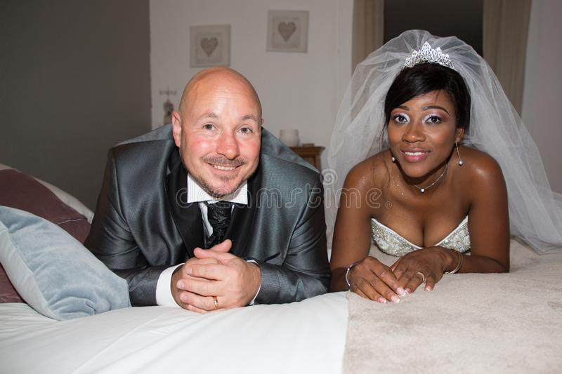 interracial couple african caucasian american bride and groom lying on bed at home in wedding royalty free stock photography