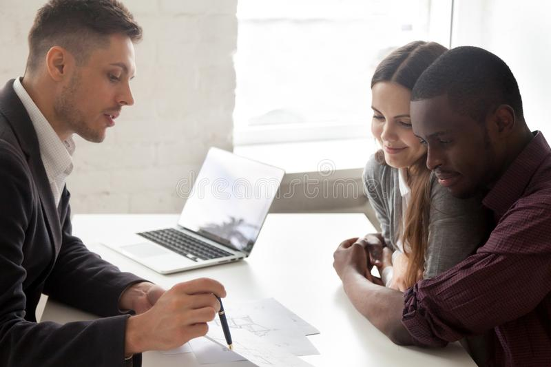 Interracial couple considering mortgage or buying house consulti. Interracial couple consider mortgage investment loan or real estate purchase consult with stock photo