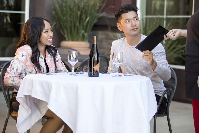 Dating Couple Paying at a Restaurant. Interracial couple on a date paying for a restaurant tab with a waitress. They are in an outdoor cafe handling the payment stock photos