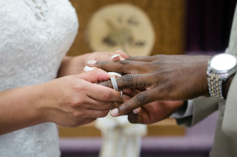 Interracial couple exchanging wedding rings and vows at marriage ceremony royalty free stock photography