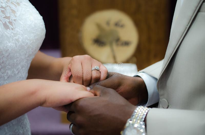 Interracial couple holding hands a the wedding altar stock image