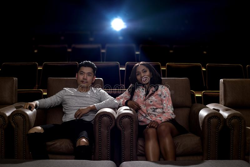Interracial couple on a movie theater date stock image