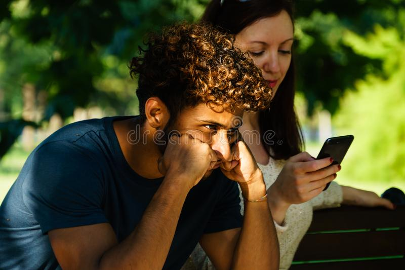 Interracial couple suffering from alienation due to a cell phone obsession. Couple on the bench in the park, female introverted with engagement in a social stock image