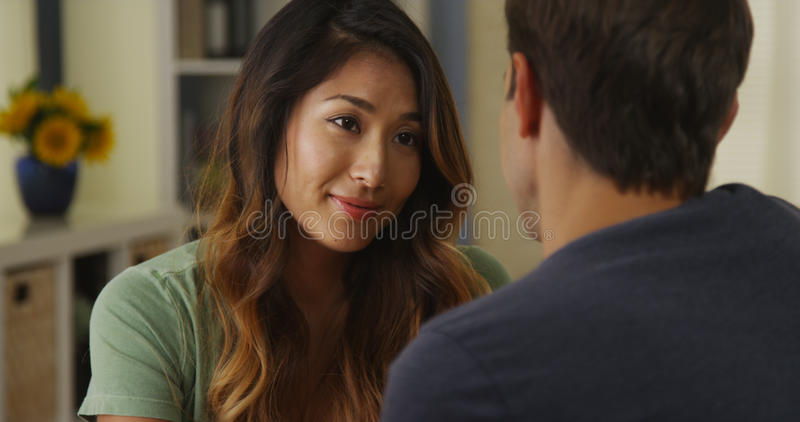 Interracial couple talking at home royalty free stock images