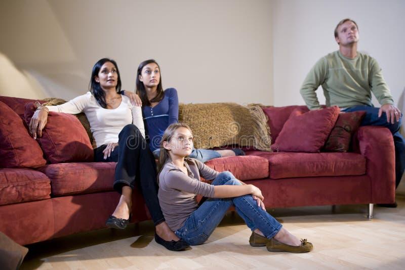 Interracial familiezitting op bank die op TV let stock foto's