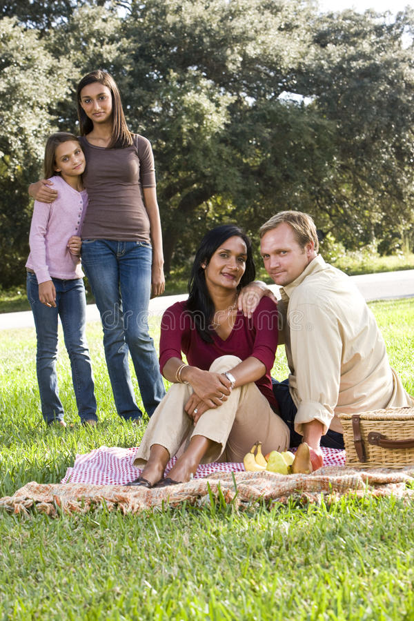 Interracial family enjoying picnic in park. Interracial family with two children having picnic on sunny day in park stock images