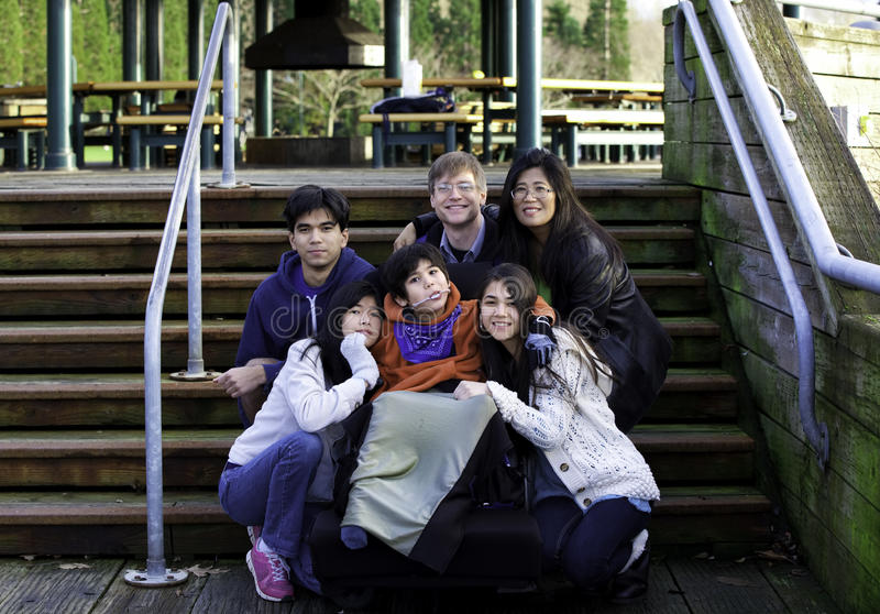 Interracial family surrounding disabled boy in wheelchair outdoors by stairs, child has cerebral palsy royalty free stock photo