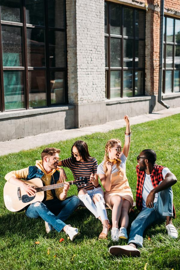 interracial group of friends with acoustic guitar resting on green grass royalty free stock photos