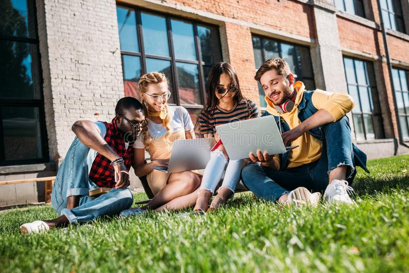 Interracial group of students with laptops and notebooks studying on green. Lawn together royalty free stock images