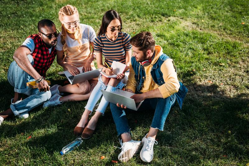 Interracial group of students with laptops and notebooks studying on green. Lawn together stock image