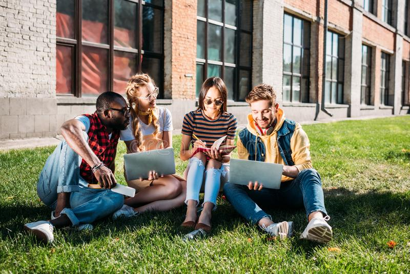 Interracial group of students with laptops and notebooks studying on green. Lawn together stock photography