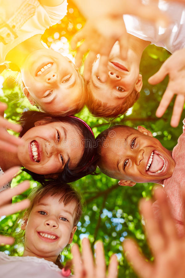 Interracial kindergarten group putting heads together royalty free stock images