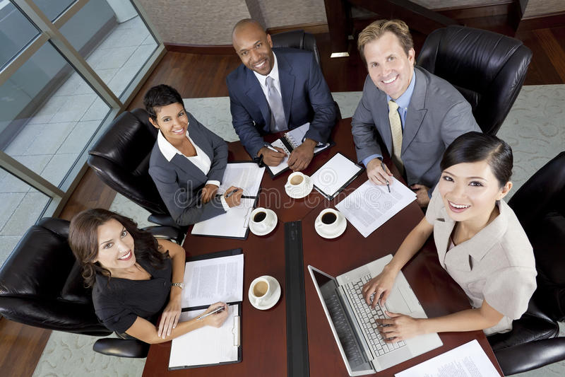 Interracial Men & Women Business Team Meeting. Interracial group of business men & women, businessmen and businesswomen team meeting in boardroom stock photography