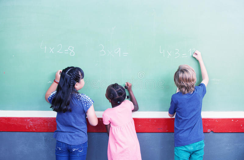 Interracial students writing numbers on chalkboard at elementary royalty free stock images