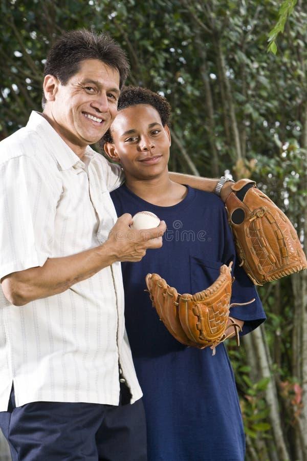 Interracial vader en zoon met honkbalhandschoenen stock afbeelding