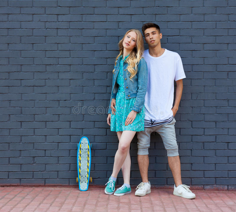 Interracial young couple in love outdoor whis skateboard. Stunning sensual outdoor portrait of young stylish fashion couple posing. Interracial very young couple stock photo