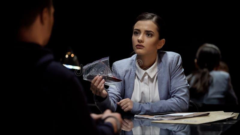 Interrogatore attraente di signora che dimostra prova sanguinosa del coltello al sospetto immagini stock libere da diritti