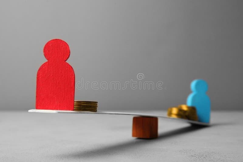 Interrupción en los ingresos de la gente de la desigualdad Monedas de oro en escalas imagen de archivo libre de regalías