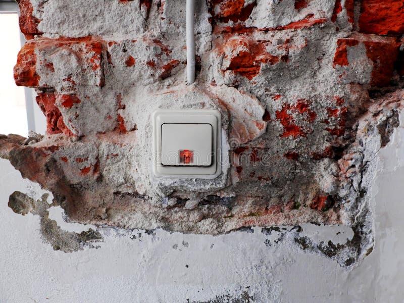 Interrupteur de lampe dans un mur avec le plâtre enlevé et les briques évidentes photos libres de droits